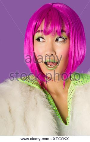 Jeune femme surprise funky en perruque rose à la vue latérale sur fond violet