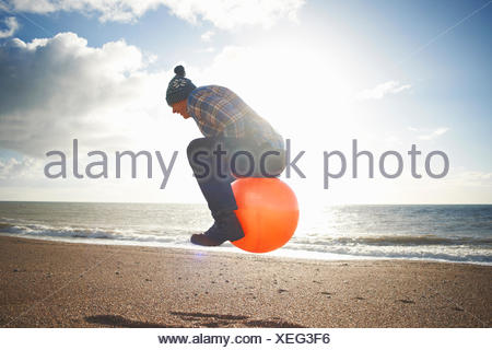 Man jumping mid air gonflable sur hopper at beach Banque D'Images