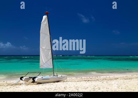 Catamarano sulla costa esotici dell'Oceano Atlantico con uno sfondo dalla sabbia dorata di acqua color smeraldo e il blu del cielo. Bellissimo mare dei Caraibi, pan Foto Stock