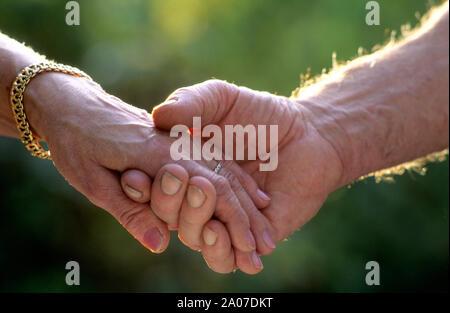 Due anziani sposati in amore tenendo le mani all'aperto