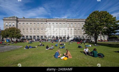 Studenti e rilassante ejoying una piacevole giornata con bel tempo sul prato al di fuori del Libro di Kells, Trinità vecchia libreria a Dublino, Irlanda. Foto Stock