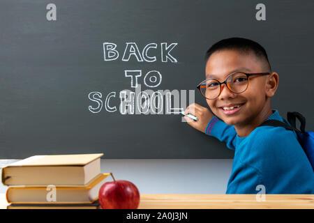 """Si torna a scuola. Ragazzo scrive sulla lavagna a fogli mobili con il testo """"Si torna a scuola"""". Foto Stock"""