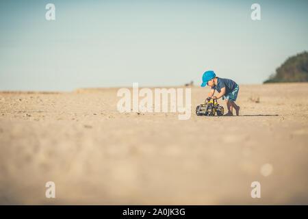 Il Toddler boy giocare con giocattoli su una spiaggia assolata. Bambino a camminare sulla sabbia. Bellissima spiaggia di ispirazione e vista oceano, paesaggio. Foto Stock