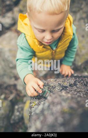 Il Toddler boy giocare con giocattoli su una roccia. Bambino passeggiate sulle montagne rocciose. Foto Stock