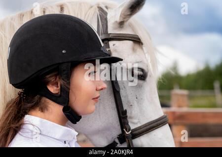 Profilo di giovane donna attiva nel casco equestre e bianco cavallo di razza pura Foto Stock