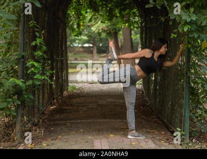 Una giovane donna in piedi in un tunnel di stretching prima di correre in un parco Foto Stock