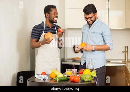 Due gli studenti di sesso maschile in abiti casual andando al frullato di cottura in piedi in cucina di hostel, tenendo pompelmo, arancio, Apple, pomodoro in mani, allegria