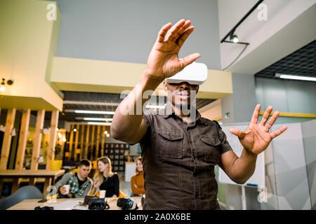 Tecnologia, giochi, intrattenimento e concetto di persone. L'uomo africano indossa casual e realtà virtuale auricolare o gli occhiali 3d, la riproduzione di video gioco Foto Stock
