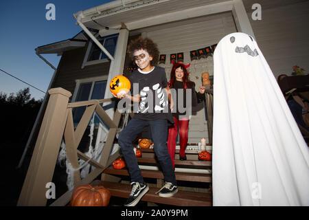 Angolo basso ritratto di bambini felici di lasciare casa trucco o trattare su Halloween, focus su sorridente ragazzo afro-americana in primo piano, shot con flash