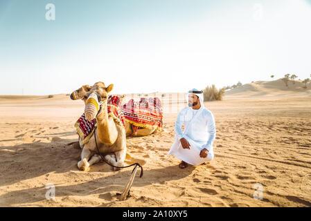 Uomo che indossa gli abiti tradizionali, tenendo un cammello sulla sabbia del deserto, a Dubai