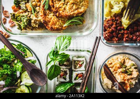 Sano cibo vegan in recipienti di vetro. Lay piatto di spezzatino con ceci, vegan bergrer, hummus, insalata di cavolo, vegan sushi panini e pane.