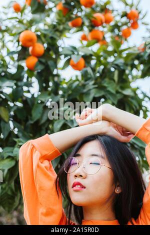 Ritratto di giovane donna asiatica, tangerine tree in background Foto Stock