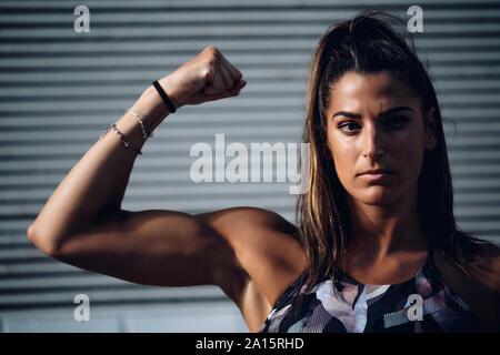 Ritratto di fiducioso giovane donna muscoli di flessione
