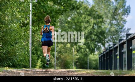 Giovane donna jogging su un sentiero di truciolo
