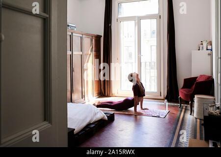 Bruna giovane donna a praticare yoga in dormitorio studenti Foto Stock