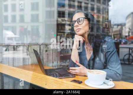 Business donna avente una pausa in un cafe e lavorare con un computer portatile Foto Stock