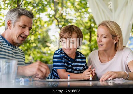 Genitori felici e figlio la riproduzione di un gioco da tavolo sulla terrazza Foto Stock