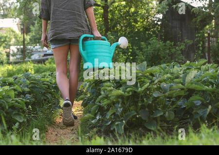 Close-up di donna con l'innaffiamento può camminare nel giardino