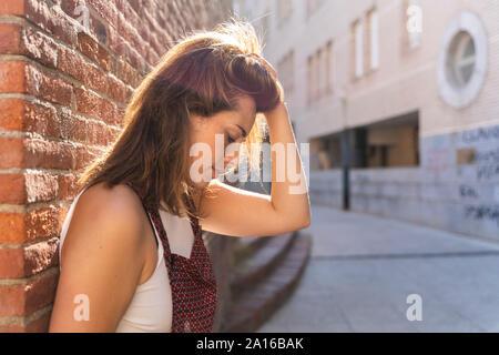 Giovane donna appoggiato su di un muro di mattoni, mano nei capelli Foto Stock