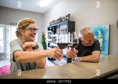 Ridendo giovane cheers durante una degustazione di vino presso un vigneto locale.