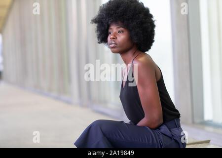 Piuttosto giovane donna africana su strade cittadine, seduta sul banco di lavoro