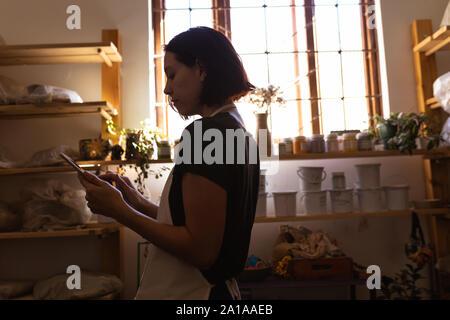 Potter femmina in un ceramiche studio utilizzando tablet