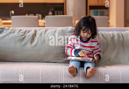 Piccola ragazza seduta sul suo divano utilizzando una tavoletta digitale Foto Stock