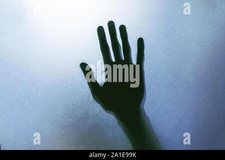 L'ombra mani di uomo dietro il vetro. Foto Stock