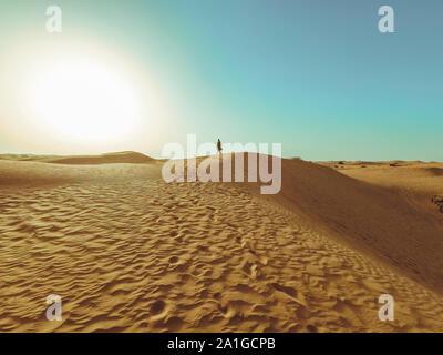 Giovane bella donna in abiti lunghi e con un cappello in mezzo al deserto di Dubai con la luce del sole.