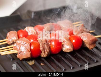 Preparazione della bistecca di balsamico spiedini con pomodori ciliegia sulla padella per grigliare Foto Stock