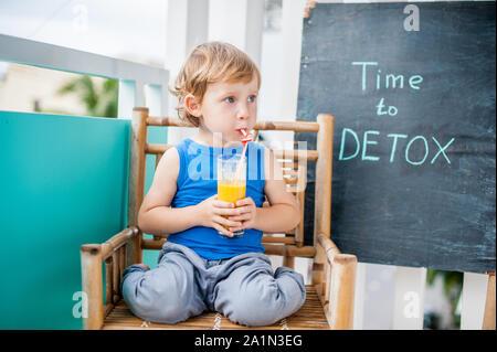 Tempo di DETOX chalk iscrizione. Il ragazzo è bere freschi, sani, detox bevanda a base di frutta. Agitare di frutta, succo di frutta fresco, frullato. Concetto di salute Foto Stock