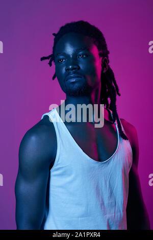 Giovane bello afro american boy con capelli eleganti che indossa una camicia bianca che cercano riposo, close up ritratto, isolato sfondo viola, studio shot. Foto Stock