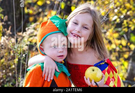 Un big sister abbraccia il suo piccolo fratello, entrambi posti in adorabili costumi di Halloween. Uno è una zucca e gli altri una principessa. Foto Stock