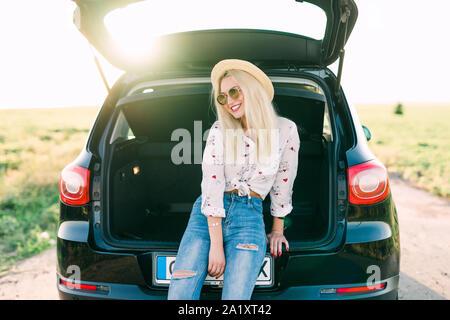 Donna seduta nel retro della vettura sorridente. Ottenere pronto ad andare. Giovani ridendo donna seduta in aprire il portabagagli di un'auto. Estate viaggio su strada. Giovane donna sitt