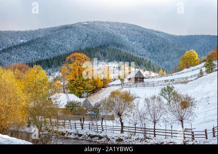 Paesaggio con la prima neve e alberi d'autunno in una montagna Foto Stock