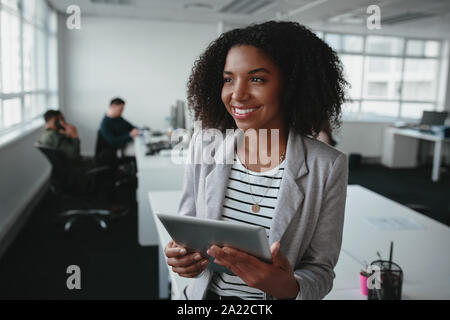 Ritratto di un successo cordiale giovane nero imprenditrice azienda digitale compressa in mano guardando lontano in ufficio Foto Stock
