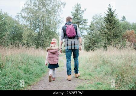 Giovane ragazza con il suo papà in mano mentre camminare attraverso la foresta