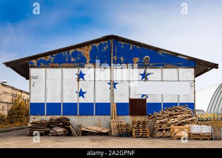 Close-up della bandiera nazionale di Honduras dipinta sulla parete metallica di un grande magazzino il territorio chiuso su un giorno d'estate. Il concetto di spazio di archiviazione Foto Stock