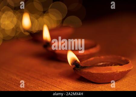 Diwali, deepawali, deepavali, deepabali è la festa delle luci. Accesa la masterizzazione Diya decorativo con bokeh isolaed in sfondo nero con copia spazio.