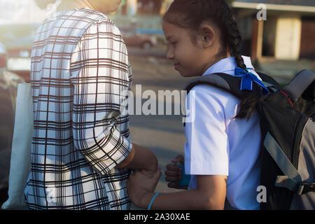 Madre e figlia stanno camminando mano nella mano a scuola sotto la luce del sole. Foto Stock
