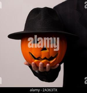 Zucca di Halloween con black hat e faccia sorridente in man mano