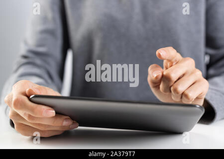Donna che utilizza computer tablet per le negoziazioni di borsa. Close-up di mani femminili di toccare lo schermo del dispositivo tablet pc. Professional investimenti online e rischio analy