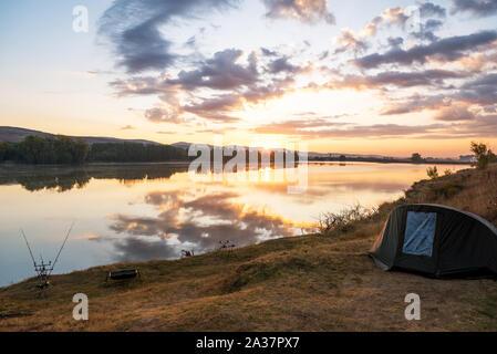 Le avventure di pesca, la pesca alla carpa. Il pescatore, al tramonto, è la pesca con carp fishing tecnica. Campeggio in riva al lago. Foto Stock