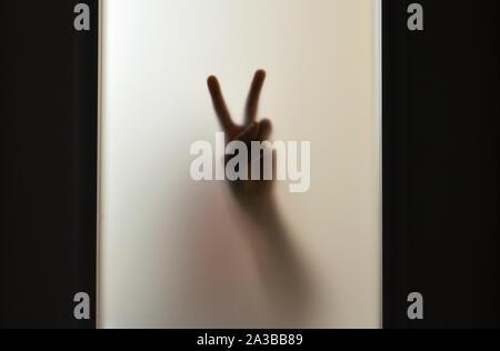 Immagini sfocate di mano mostra segno di vittoria attraverso un vetro smerigliato Foto Stock