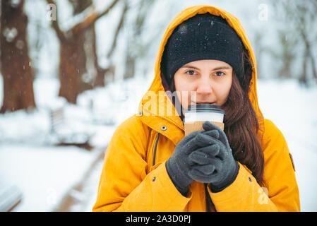 Donna di bere il caffè al di fuori del parco in verticale. bere andare. inverno. warm up Foto Stock