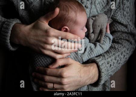 Un padre tiene il suo Figlio bambino sul suo petto. Famiglia bonding. Paternità