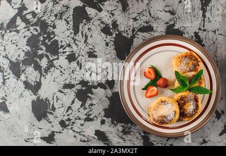 Colazione Gourmet - frittelle di cagliata, cheesecake, cagliata pancake con fragole, menta e zucchero a velo in una piastra bianca. Messa a fuoco selettiva. Vista superiore