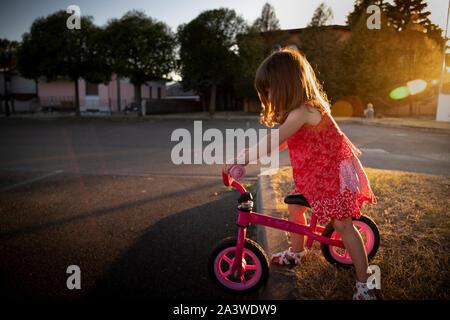 Bambino Toddler girl equitazione dinamica la sua bici nelle aree urbane posizione esterna con golden la luce del tramonto Foto Stock