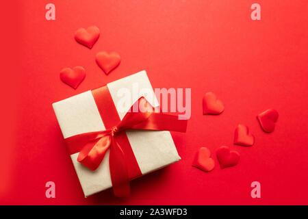 Il giorno di San Valentino del concetto. Cuori rossi, kraft sorpresa box con prua su uno sfondo di colore rosso. Appartamento laico, vista dall'alto, spazio di copia Foto Stock