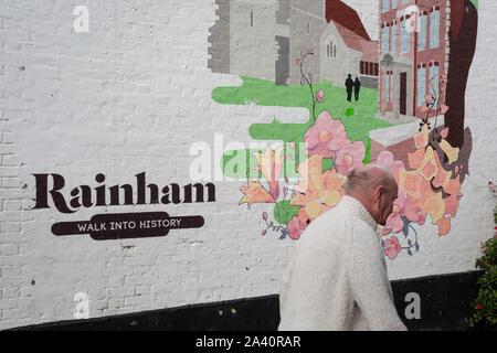 Un locale uomo cammina passato un opera d arte murale che mostra la piccola cittadina di Essex di Rainham, del 8 ottobre 2019, a Rainham, Essex, Inghilterra. Gli elettori in questo Havering borough votato il 69% a favore di Brexit durante il referendum del 2016. Foto Stock